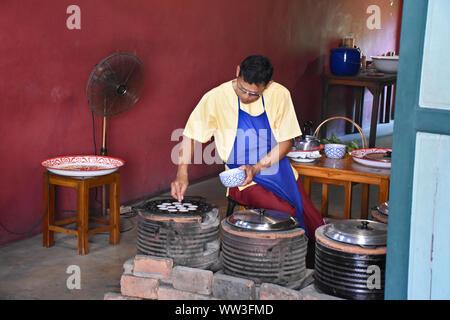 Kanchanaburi, Thailand, 09.09.2019: A local Thai man is preparing Thai coconut pancakes in a traditional way in the heritage village 'Mallika City R.E - Stock Photo