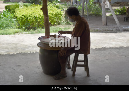 Kanchanaburi, Thailand, 09.09.2019: A local Thai man in traditional Thai, Siamese dress is sorting rice, separating the bad ones from the good ones in - Stock Photo