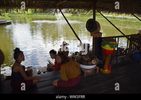 Kanchanaburi, Thailand, 09.09.2019: Local Thai people in traditional Thai, Siamese dresses are resting and eating on the lake on a floating house in t - Stock Photo