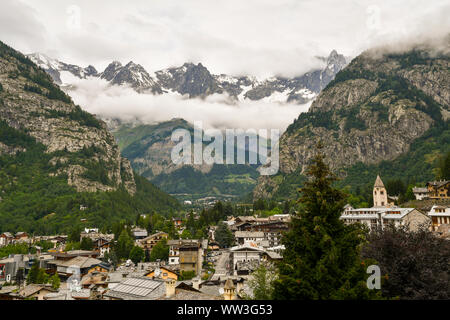 Elevated view of Courmayeur city at the foot of the Mont Blanc mountain range with a cloudy sky in summer, Aosta Valley, Alps, Italy - Stock Photo