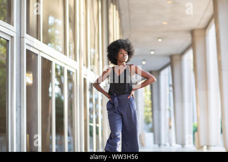 A young fashionable Afro-American woman walking down the street with her hands on her waist - Stock Photo