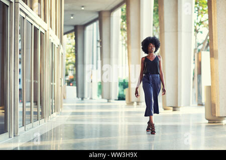 A young fashionable Afro-American woman confidently walking down the hall outside the financial building - Stock Photo