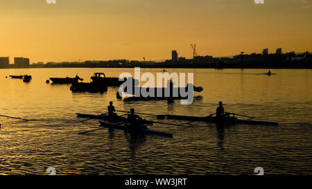 Pictured are canoeists at sunrise on the River Thames at London City Airport - Stock Photo