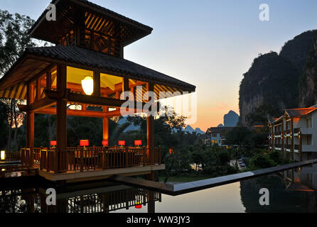 The karst geologic rock formations and chinese architecture in Yangshuo at sunset, Guangxi province, China. - Stock Photo