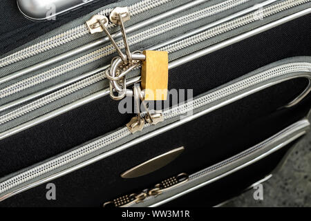 Zippers locked with a padlock on a black travel suitcase. Protect the baggage from theft during the trip. Luggage theft prevention. - Stock Photo