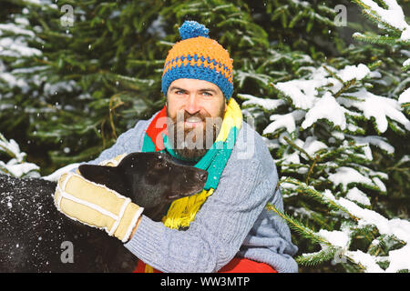 Macho with beard and mustache hugs dog. Man wears knitted hat, scarf and gloves with black dog.Guy with smiling face with firtrees covered with snow on background, defocused. Winter walks concept. - Stock Photo