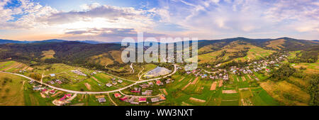 Aerial drone view of urban village Pidbuzh in Carpathians, Ukraine. 180 degrees panoramic landscape of rural area. Sunset time, end of summer. - Stock Photo
