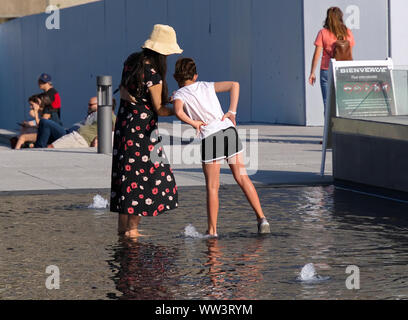 Montreal, Canada. Jul 2019. Mother and daughter looking at selfies photos while both barefoot in a shallow water fountain pool. - Stock Photo