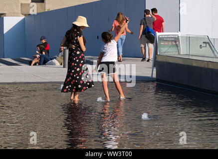 Montreal, Canada. Jul 2019. Daughter showing mom some dance moves while both barefoot in a shallow water fountain pool. - Stock Photo