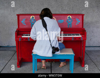 Montreal, Canada. Jul 2019. Young woman photographer taking a breather and playing tunes on a bright red hand decorated public piano. - Stock Photo