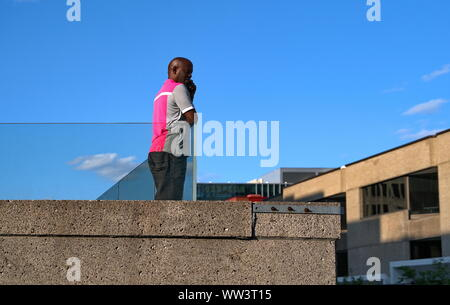 Montreal, Canada. Jul 2019. A Black Canadian man watching the festivities below from a rooftop building. - Stock Photo
