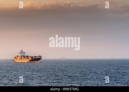 Manila, Philippines - March 5, 2019: Evening twilight shines on black and red Seaspan Ningbo container ship sailing into South Harbor. - Stock Photo