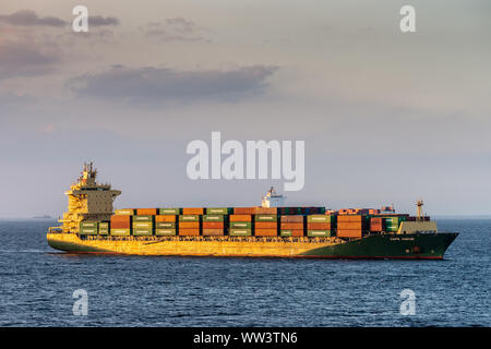 Manila, Philippines - March 5, 2019: Evening twilight shines on green and red Cape Mayor container ship sailing into South Harbor. - Stock Photo