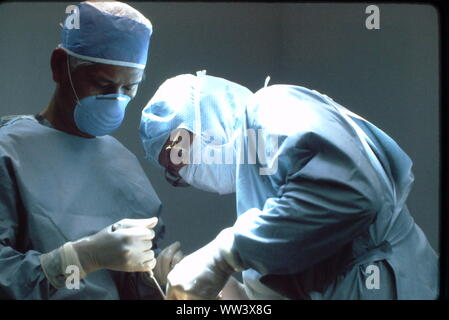 Surgeons performing knee replacement  in sterile surgical scene. - Stock Photo