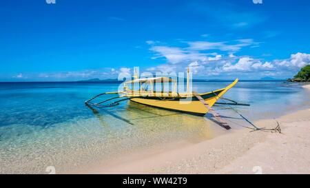 A beautiful tropical island scene with a traditional Filipino wooden outrigger boat called a banca, anchored in clear shallow turquoise water on a whi - Stock Photo