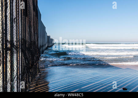 Close-up view of the international border wall extending out into the ocean between San Diego, California and Tijuana, Mexico at Border Field Park. - Stock Photo