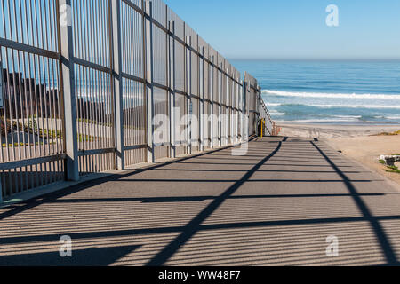 Inner fence of the international border wall which extends out into the Pacific ocean and separating San Diego, California from Tijuana, Mexico. - Stock Photo