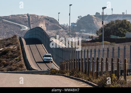 Border Patrol vehicle patrolling along the fence of the international border between San Diego, California and Tijuana, Mexico - Stock Photo