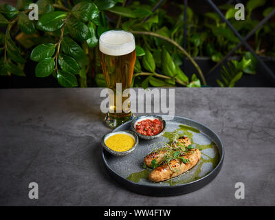 delicious sausages with sauce on a plate with beer - Stock Photo