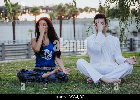 Caucasian man and Latin woman meditate in a park in Madrid. Concentration and relaxation in couple. - Stock Photo