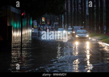 Murcia, Spain. 13th Sep, 2019. Cars drive along a flooded street in Murcia after the torrential rains fallen, eastern Spain, 13 September 2019. A man has died in Almeria rising the number of victims of the 'gota fria' (cold drop) phenomenon in the Mediterranean coast to three. The eastern regions of Valencia and Alicante continue under red level alert due to torrential rains while the State Meteorological Agency AEMET has reduced the alert in Murcia to orange level. Credit: Marcial Guillen/EFE/Alamy Live News - Stock Photo