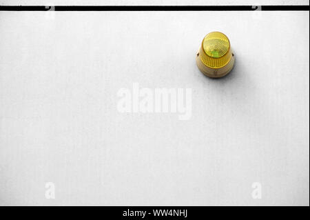 Photography of a yellow warning lamp on a smooth concrete wall, - Stock Photo