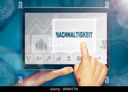 A hand holiding a computer tablet and pressing a Sustainability 'Nachhaltigkeit' business concept.
