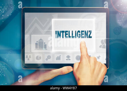 A hand holiding a computer tablet and pressing a Intelligence 'Intelligenz' business concept.