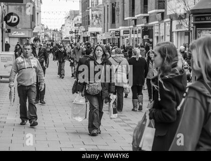 Black & White view of people walking through a busy pedestrianised shopping centre in Worthing, West Sussex, England, UK. - Stock Photo
