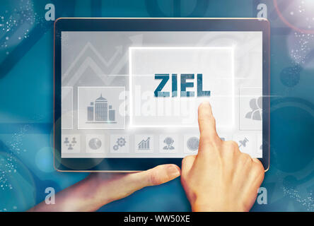 A hand holiding a computer tablet and pressing a Aim 'Ziel' business concept.