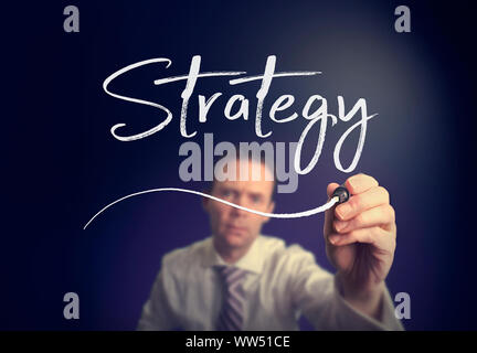A businessman writing a Strategy concept with a white pen on a clear screen. - Stock Photo
