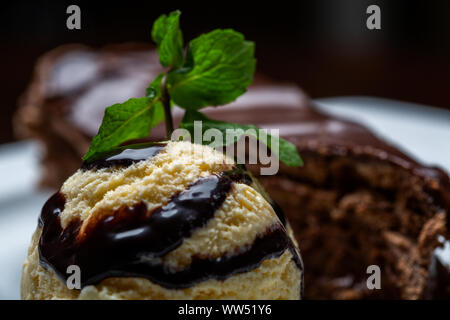 Yellow ice cream ball with chocolate topping and slice of chocolate cake. Forming a gourmet dessert. - Stock Photo