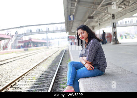 Happy young Indian girl sitting on railway station, waiting for train - Stock Photo