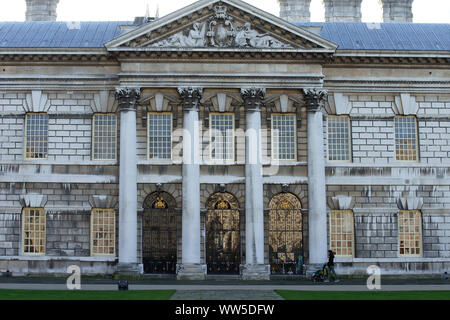 A guest of the royal Naval college in Greenwich passing the gilt front doors with a pram, - Stock Photo