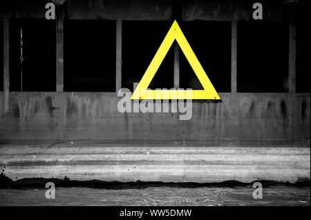 A yellow warning triangle on the steel wall of a sluice, - Stock Photo