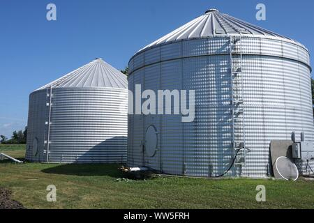 Two silver silos against a blue sky - Stock Photo