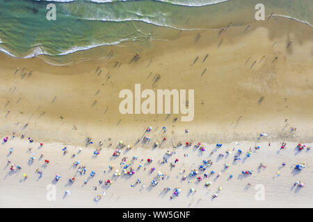 aerial view of sandy beach with colorful umbrellas and tourists swimming in beautiful clear sea water at sunny day, top view - Stock Photo