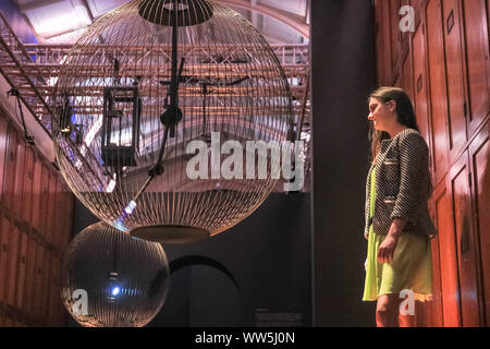 London, UK, 13th Sep 2019. An assistant engages with 'Affinity in Autonomy', an interactive installation by Sony Designs which looks at the future of AI and allows visitors to engage with a robotic pendulum. London Design Festival runs from 14-22 September 2019. Credit: Imageplotter/Alamy Live News - Stock Photo