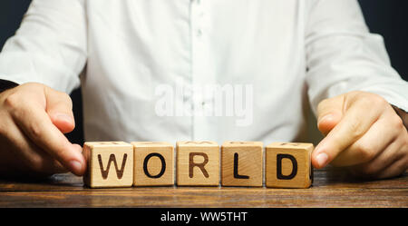 A man puts wooden blocks with the word World. The concept of globalization and global business. International relationships. Diplomacy. Investments an Stock Photo