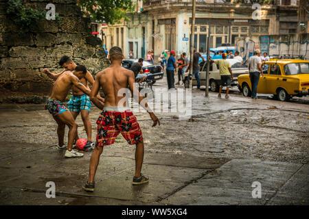 Young men playing football on the street, Havana, Cuba - Stock Photo