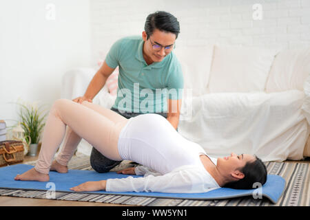 Asian young Husband help his wife exercise by yoga in living room at house. Happy family concept. - Stock Photo