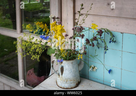 Colourful mixed bouquet of withering summer wildflowers in rusty metal coffeepot on counter against aqua tiled wall - Stock Photo