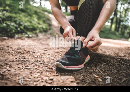 Cropped image of young athlete woman prepare to running outdoor on the forest path. Slim athletic girl ties up shoelaces on sneakers before training i - Stock Photo