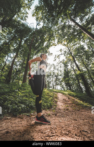 Low angle image of young woman athlete making warm-up before training in the woods. Side view of slim fit female preparing to run on forest path - Stock Photo