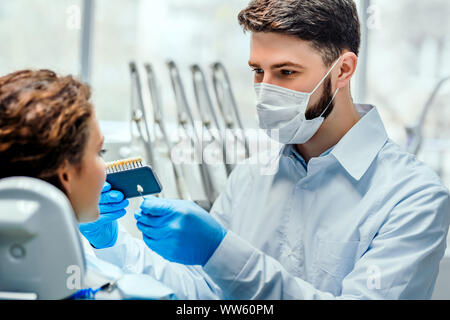 Dentist selecting patient's teeth color with palette in clinic. Side view. - Stock Photo