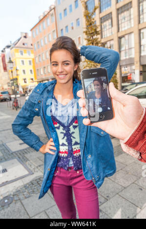 Young woman can be photographed with smartphone - Stock Photo