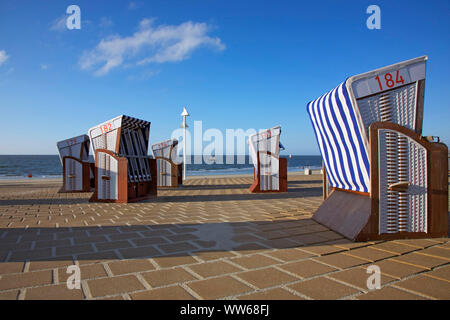 Beach chairs on the promenade on the west beach of the island Norderney. - Stock Photo