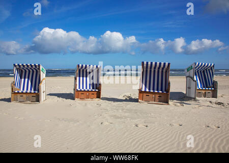 Beach chairs at the white dune on the north beach of the island Norderney. - Stock Photo
