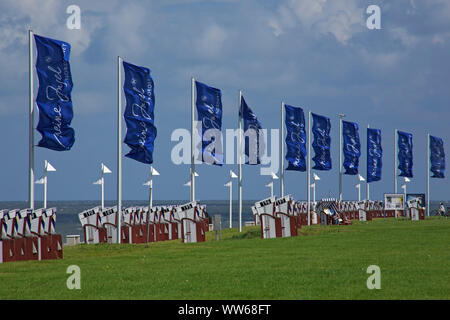 Beach chairs and flags 'Meine Insel' on the promenade on the west beach of the island Norderney. - Stock Photo