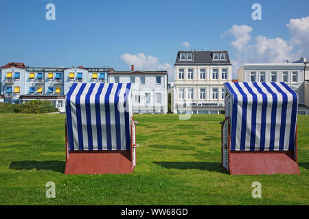 Beach chairs on the meadow on the west beach of the island Norderney. - Stock Photo
